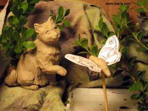 A clay-sculpted cat plays with a paper moth, diorama for sculptural reference created by Theresa Bayer