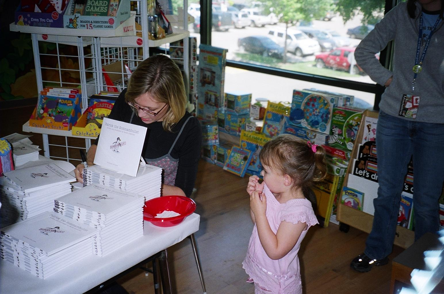 """Author-illustrator Sarah Ackerley signs """"Patrick the Somnambulist"""" (Blooming Tree Press) for a young fan at Bookpeople."""