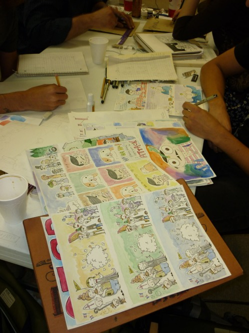 """Colored comic panels (watercolor washes) on the comic strip """"The Ortolan"""" created by a collaborative team,  Jason Poland, and Austin Havican, whose hands you see here. They described their work as deceptively simple child-like and simply but """"definitely not child-friendly."""" See more of their work at www.robbieandbobby.com. S"""