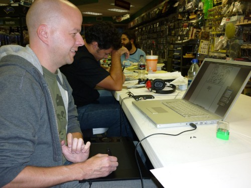 Erik Kuntz laughs at one of his digital cartoons as he draws on a Wacom tablet, while Justin Rogers works with traditional comic artist materials -- paper, pencil, eraser, pen, triangle, T-square, etc.