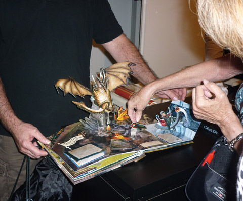 """Bruce Foster opens a spread from """"Harry Potter - a Pop-Up Book"""" for a museum goer"""